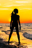 Silhouette of a girl on the beach at sunset Royalty Free Stock Photo