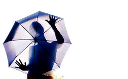 Silhouette of a girl behind an umbrella. Silhouette of a young girl hidden behind a blue umbrella Stock Photo