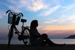 Silhouette girl with bicycle. Silhouette of the girl with a bicycle on the background of the sea sunrise royalty free stock photos