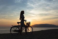 Silhouette girl with bicycle. Silhouette of the girl with a bicycle on the background of the sea sunrise stock photo