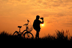 Silhouette of girl with bicycle on grass field. At the sky sunset, color of vintage tone and soft focus concept journey Royalty Free Stock Photo
