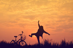 Silhouette of girl with bicycle on grass field Royalty Free Stock Photo