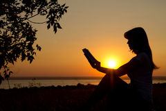 Silhouette of a girl with a book in hands at sunset Stock Photo