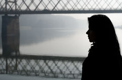 Silhouette of girl and bridge over river on beautiful autumn day Stock Images