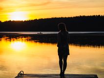 Silhouette of a girl on the bridge by the river at sunset royalty free stock photos