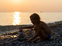 Silhouette of girl builds pyramid from stones Stock Photo