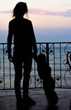 Silhouette of girl and child on the background of the sea and th Royalty Free Stock Photos