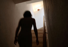 Silhouette of girl climbing steps up next floor with low time exposure. Woman walking up on stairs on a slightly movement on low exposure and dark image Royalty Free Stock Photos