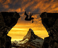 Silhouette girl climbs on a rope over an abyss. In the background Matterhorn royalty free stock photography