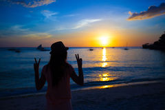 Silhouette of girl at colorful sunset on the Stock Photo