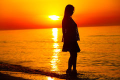 Silhouette of a lady dancing by the sea Stock Photography