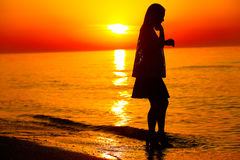 Silhouette of a lady dancing by the sea Stock Photos