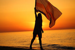 Silhouette of a girl dancing with a flag. Silhouette of a girl dancing on the beach at sunrise and holding a flag in her hand Royalty Free Stock Photography