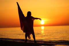 Silhouette of a girl dancing with a flag. Silhouette of a girl dancing on the beach at sunrise and holding a flag in her hand Royalty Free Stock Photo