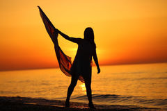 Silhouette of a girl dancing with a flag. Silhouette of a girl dancing on the beach at sunrise and holding a flag in her hand Stock Images