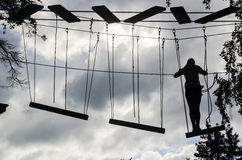 Silhouette of the girl on Dangerous ropeway with tether in rope Royalty Free Stock Images