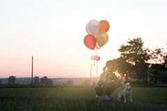 Silhouette girl with dog. And ballloon on sunset background Royalty Free Stock Photo