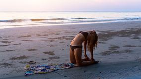 Silhouette girl doing exercise on the background of the stunning sea Stock Photos