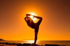 Silhouette of girl doing exercises at the coast. Silhouette of happy girl doing morning exercises against sunrise at the sea coast Royalty Free Stock Photo