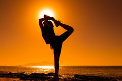 Silhouette of girl doing exercises at the coast. Silhouette of happy girl doing morning exercises against sunrise at the sea coast Stock Photography