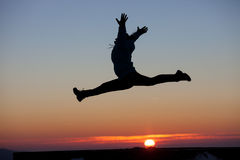 Silhouette of girl doing the splits jump in sunset Royalty Free Stock Photos