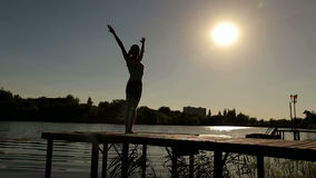 Silhouette of girl doing yoga at a beautiful lake. stock video footage