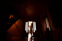 Silhouette of the girl in the doorway of the house Stock Photography