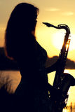 Silhouette of a girl in a dress with a brass musical instrument in his hands looking thoughtfully into the distance stock images