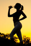 Silhouette of girl drinking water after outdoor workout royalty free stock photography