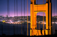 Golden Gate Bridge and Silhouette. A silhouette of a girl eclipsed by a single tower of the brightly lit Golden Gate Bridge. Behind them both is a small chunk of Royalty Free Stock Photos