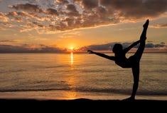 Silhouette of girl enjoying her morning dance exercise at a beach sunrise