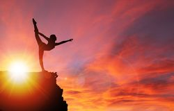 Silhouette of Girl Exercising on Edge of Cliff at Sunrise stock photos