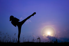 Silhouette of girl exercising side kick in the nature. On moon sky and cloud Stock Images