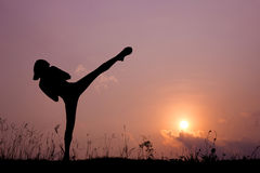 Silhouette of girl exercising side kick. Stock Photos