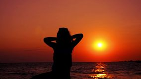 Silhouette of a girl exercising at sunset stock video