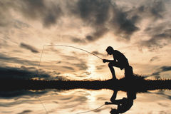 Silhouette of girl fishing. During sky sunset Royalty Free Stock Photos