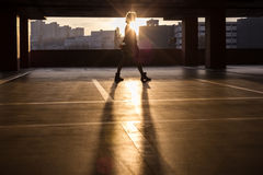 Silhouette of  girl. Girl sweeping the parking lot for cars Royalty Free Stock Images