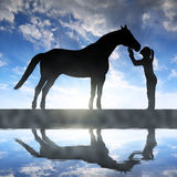 Silhouette of a girl giving a kiss horse. In sunset stock photo