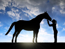 Silhouette of a girl giving a kiss horse. In sunset stock images