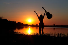Silhouette of girl with a guitar on a sunset Royalty Free Stock Photos