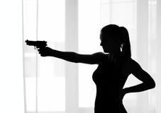 Silhouette of the girl with a gun Stock Photos