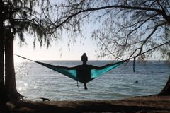 Silhouette of a girl in hammock stock photography