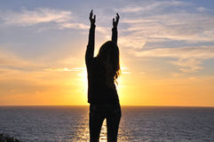Silhouette of a girl with hands up Stock Photos