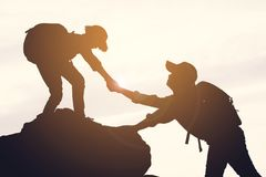 Silhouette of girl helping a boy on the top mountain. At the sky sunset Royalty Free Stock Photos
