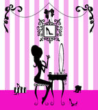 Silhouette of a Girl at her Vanity. Fashion illustration of a pretty girl at her vanity applying makeup Stock Photo