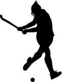 Silhouette of girl hockey player hitting ball Royalty Free Stock Photos