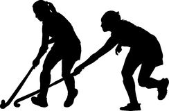Silhouette of girl hockey players battling for possession Stock Photo