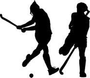 Silhouette of girl hockey players hitting  Royalty Free Stock Photo