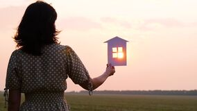 Silhouette of a girl holding a model of a paper house in her hand. The rays of the sun during sunset pass through the