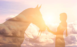 Silhouette of a girl and a horse on a background of the sky. With clouds stock photo